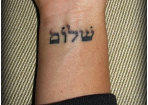 "A tattoo of the Hebrew word ""Shalom,"" which means ""peace."""